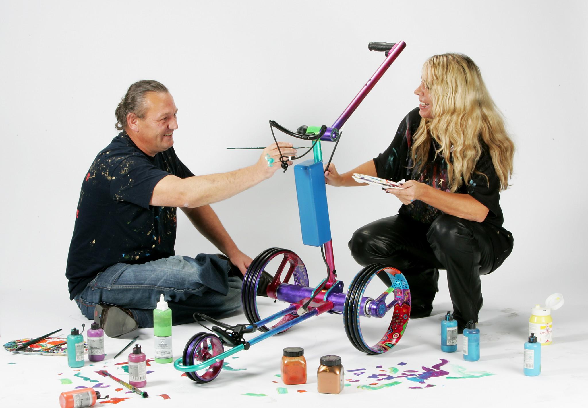 zwei Menschen bemalen einen Golf Trolley im Hundertwasser-Look